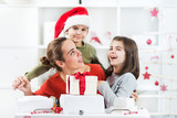 Two kids and their mother are opening Christmas pressents in their lliving room. They are having a lot of fun.