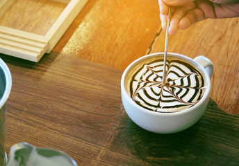 Making mocha art with chocolate in vintage tone and flare effect