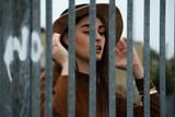 Ragazza con cappello dietro il cancello
