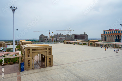 Poster View over square and buildings under construction next to Turpan train station,