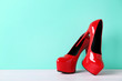 Pair of red women's high-heeled shoes on wooden table