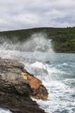 Морской берег. Брызги воды на скалу.