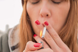 smoking young woman lighting cigarette outdoors close up. concept of nicotine addiction by teenagers