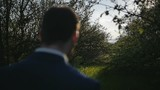 groom walking spring park with trees close-up of shoulders and head shot slow motion