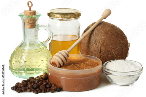 Foto Murales Body scrub of ground coffee, honey  and coconut oil in jar on white isolated background, homemade cosmetic for peeling and spa care