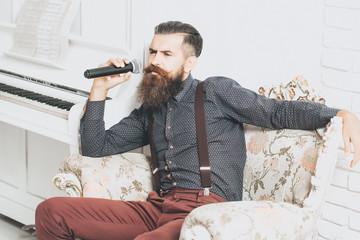 Handsome man singing in armchair