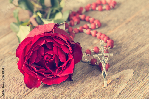 Religion concept with rose and rosary