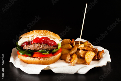 Poster fresh tasty burger and french fries on wooden table.  potato wed