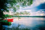 Łódka i jacht w blasku chmur i jeziora