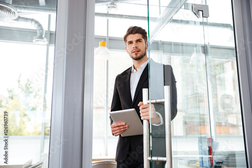 Poster Businesman with tablet entering the door in office