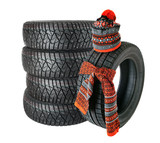 Rubber tire with a knotted scarf and winter hat. Isolated. Set of wheels with winter, studded tires. isolated