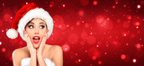 Attractive Woman With Santa Hat Looking Surprised And Amazed