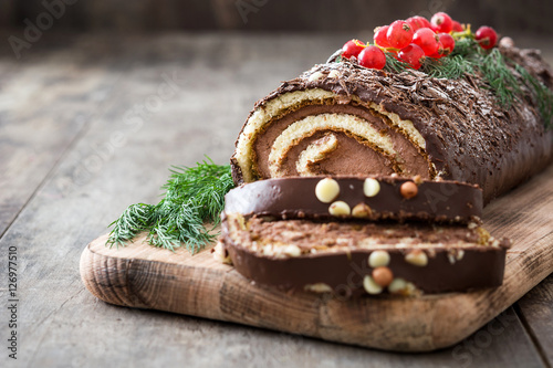 Chocolate yule log christmas cake with red currant on wooden background