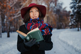 Young woman with red hat holding and reading poetry book in winter forest background