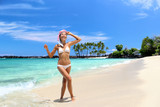 Beach vacation woman enjoying swimming coming out of turquoise ocean water walking with snorkel mask relaxing on perfect white sand travel destination. Asian bikini girl happy for relaxation holiday.