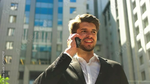 Serious young businessman wearing black suit and white shirt, talking on mobile phone.