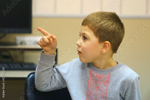 Plakat Portrait of handsome caucasian boy sitting at chair indoor and pointing his finger up