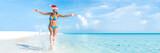 Christmas beach holiday travel banner panorama background for Christmas vacation fun. Bikini woman running carefree splashing water enjoying swim caribbean travel getaway with santa hat.