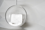 Transparent glass chair against a white wall with geometric shapes.
