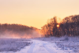 Winter misty colorful sunrise. Rural foggy and frosty scene.
