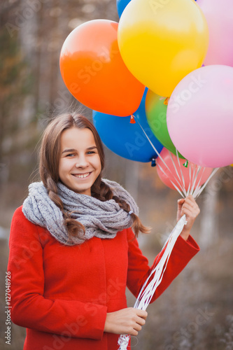 Poster Beautiful teenager girl with colorful balloons in autumn park