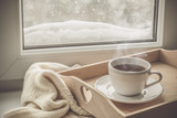Tea on tray and sweater in from of snowing winter