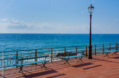 Fotobehang Liguria two benches and an old lantern on the walking promenade of Nervi, Genoa, in Italy with a wonderful view to the Mediterranean Sea on a sunny day with a boat visible far away on the horizon