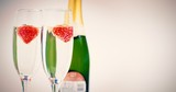 Two champagne flutes with floating strawberries