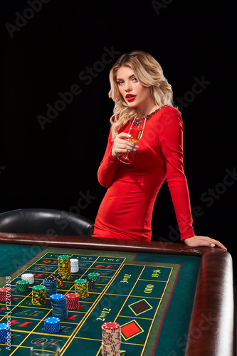 girl in a red dress with  glass in his hand playing Roulette плакат