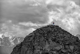 Silhouette of a girl with backpack on huge mountain. Very far. Epic black-and-white photo. - 127088502