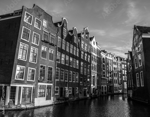 Poster AMSTERDAM, NETHERLANDS - JANUARY 15, 2016: Black-white photo of famous buildings of Amsterdam city centre close-up at sun set time
