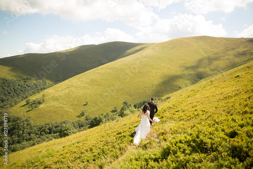 Poster Beautiful gorgeous bride posing to groom and having fun, luxury ceremony at moun