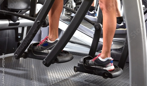 Legs on elliptical trainer © Kurhan