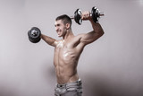 Young man bodybuilder exercise dumbbells arms.