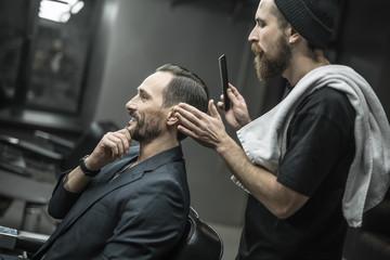 Making hairstyle in barbershop