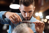 Fototapety Close up of young male hairdresser cutting hair