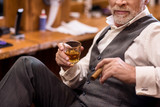 Close up of senior man with whiskey glass and cigar