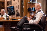 Elegant senior man with whiskey glass and cigar at barbershop