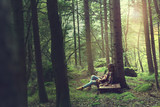 traveler woman rests in a mysterious and surreal forest