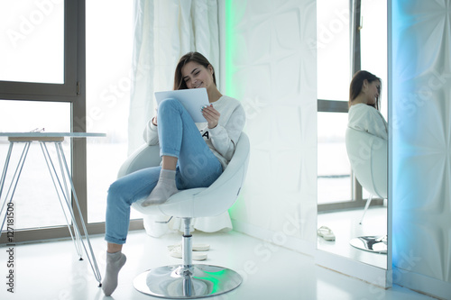 Poster Woman sitting at comfortable home chair with her tablet PC