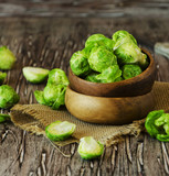 Green raw Brussels sprouts in a wooden bowl , selective focus