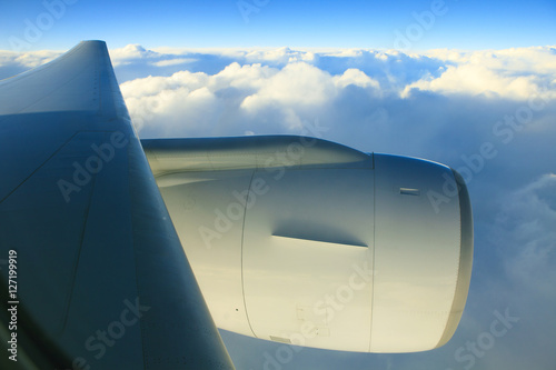 Poster air plane engine and wing floating over white cloud and blue sky