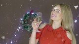 Blonde lady in red dress with champagne flute and mask at the Christmas background