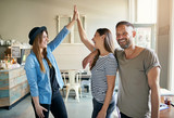 Two women putting up high fives with male friend