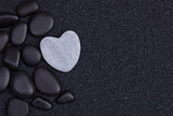 Black stones with grey zen heart shaped rock on  grain sand