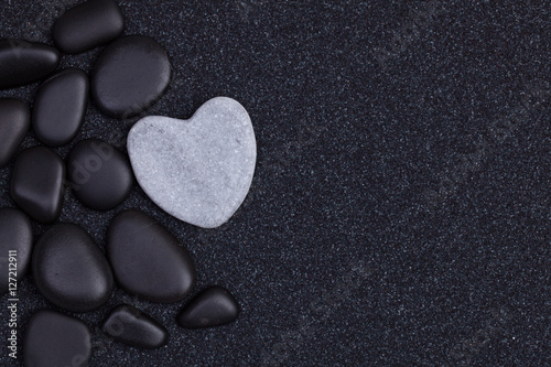 Foto op Plexiglas Stenen in het Zand Black stones with grey zen heart shaped rock on grain sand