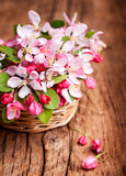 Spring flowers in a straw basket on a wooden surface