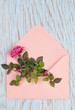 Top view of a pink envelope with rose flower in it