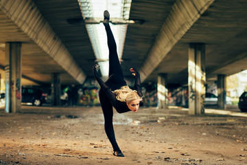 Attractive jazz ballerina dancing under the overpass