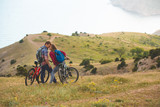 young couple  riding bikes in the mountains